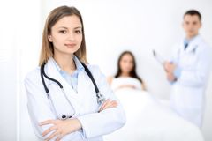 Medicine doctor standing and smiling on the background with patient in the bed stock photos