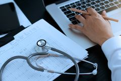 Medicine doctor. Stethoscope with heartbeat report, analyzing checkup on laptop royalty free stock photos