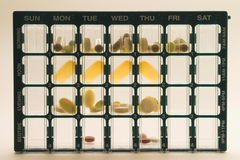 Daily Medicine Dose Organizer Pillbox Backlighted. Organizer for medications with compartments for keeping track of daily doses of medicine over a week timespan stock image