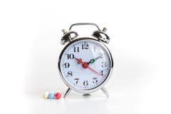 Medicine e sveglia immagine stock