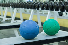 Medicine exercise balls. Sitting on a weight bench, with dumbbells in background as might be found at a gym or club Royalty Free Stock Photo