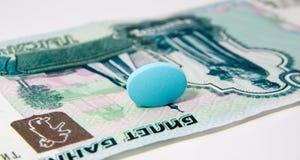 Medicine fot money. The medicine tablet lies on money Royalty Free Stock Image