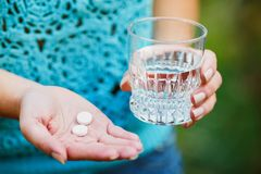 Medicine, health care and people concept - close up of woman taking in pill stock image
