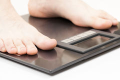 Medicine, healthcare and all things related. Man standing on weight scales with bare foot Stock Photos