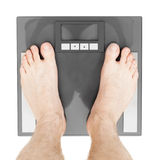 Medicine, healthcare and all things related. Man standing on weight scales with bare foot - view from top Stock Photo
