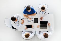 Doctors with cardiogram and computers at hospital Royalty Free Stock Photos