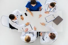 Group of doctors with cardiograms working at table Stock Photos