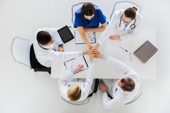 Group of doctors holding hands together at table Royalty Free Stock Photography
