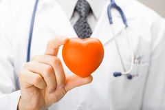 Medicine and healthcare - doctor holding toy heart with two fingers Stock Photography