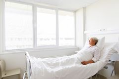 Sad senior woman lying on bed at hospital ward stock photo