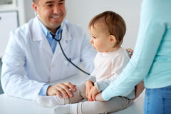 Doctor with stethoscope listening baby at clinic. Medicine, healthcare, pediatry and people concept - doctor with stethoscope listening to baby on medical exam Royalty Free Stock Photos