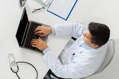 Doctor with cardiogram and laptop at clinic Royalty Free Stock Image