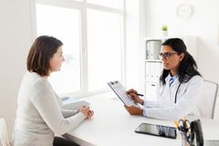 Doctor with clipboard and woman patient at clinic Royalty Free Stock Photos