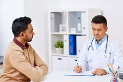 Doctor and male patient meeting at hospital. Medicine, healthcare and people concept - doctor with clipboard and young male patient having health problem meeting Stock Photography