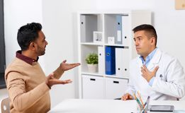 Doctor and displeased male patient argue at clinic. Medicine, healthcare and people concept - doctor and displeased male patient arguing at clinic Stock Photo