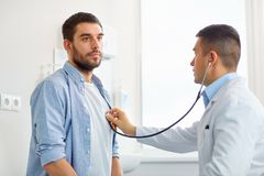 Doctor with stethoscope and patient at hospital Stock Images