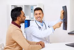 Doctor with x-ray and male patient at clinic. Medicine, healthcare and people concept - happy doctor or surgeon showing x-ray to male patient at clinic Royalty Free Stock Photo