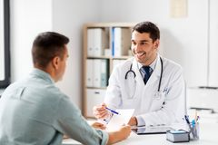 Doctor showing prescription to patient at hospital. Medicine, healthcare and people concept - happy smiling doctor showing prescription to patient at medical royalty free stock image