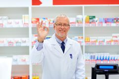 Senior apothecary at pharmacy showing ok hand sign. Medicine, healthcare and people concept - senior apothecary at pharmacy cash register showing ok hand sign Royalty Free Stock Photos