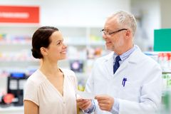 Apothecary and woman with prescription at pharmacy. Medicine, healthcare and people concept - senior apothecary with prescription talking to female customer at stock photography