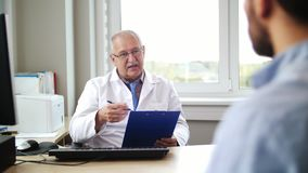 Senior doctor talking to male patient at hospital. Medicine, healthcare and people concept - senior doctor with clipboard  talking to young male patient having stock footage