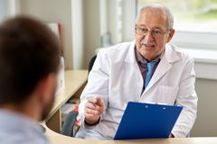 Senior doctor talking to male patient at hospital. Medicine, healthcare and people concept - senior doctor with clipboard talking to young male patient having royalty free stock image