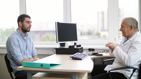 Senior doctor talking to male patient at hospital. Medicine, healthcare and people concept - senior doctor talking to young male patient having health problem at stock footage