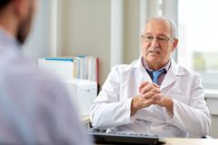 Senior doctor talking to male patient at hospital. Medicine, healthcare and people concept - senior doctor talking to young male patient having health problem at Royalty Free Stock Photo