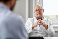 Senior doctor talking to male patient at hospital. Medicine, healthcare and people concept - senior doctor talking to young male patient having health problem at stock image
