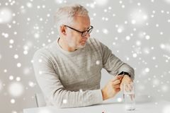 Senior man with water and pill looking at watch. Medicine, healthcare and people concept - senior man with glass of water water and pill looking at wristwatch or Stock Photo