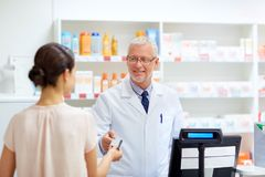 Apothecary taking customer credit card at pharmacy. Medicine, healthcare and people concept - smiling senior apothecary taking credit card from customer at royalty free stock photography