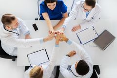 Group of doctors making high five at table Royalty Free Stock Images