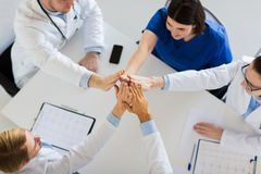 Group of doctors making high five at table Stock Image