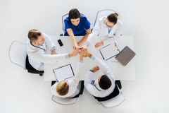 Group of doctors making high five at table Stock Photos