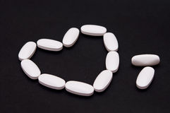 Medicine heart pills. Medicine pills and on a dark background (selective focus on the pills stock photography