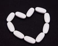 Medicine heart pills. Medicine pills and on a dark background (selective focus on the pills Royalty Free Stock Image