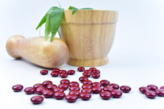 Medicine and Herbal in Wooden Mortar on white Background. Medicine pill and Herbal in Wooden Mortar on white Background Stock Images