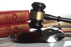 Medicine law concept. Law books with wooden judges gavel and medical stethoscope on white table in a courtroom or enforcement office, close-up. selective focus royalty free stock photography