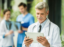 Medicine. Mature male doctor looking at digital tablet. Healthcare and medicine concept Royalty Free Stock Photo