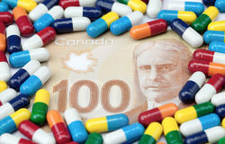 Medicine and Money. Hundred dollar Canadian bill covered with colorful pills on a white background Royalty Free Stock Photos