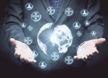 Medicine and network concept. Businessman holding polygonal globe with abstract glowing medical icons on dark background. Medicine and network concept. 3D Vector Illustration