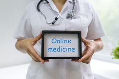 Medicine online text in the hands of a female doctor royalty free stock photo