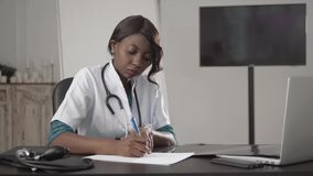 Medicine, people and healthcare concept - happy female african american doctor or nurse writing medical report to. Clipboard at hospital stock images