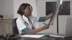 Medicine, people and healthcare concept - happy female african american doctor or nurse writing medical report to stock video footage