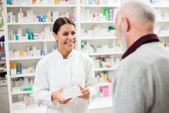 Happy female pharmacist giving medications to senior male customer stock images