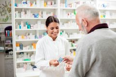 Smiling young female pharmacist giving prescription medication pills to senior male patient royalty free stock image