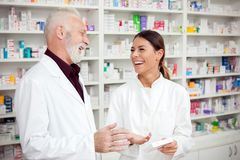Happy young female and senior male pharmacists standing in front of shelves with medications and talking royalty free stock image