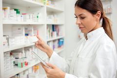 Serious young female pharmacist taking medications from the shelf royalty free stock photography
