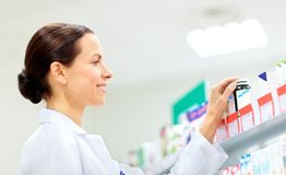 Happy female apothecary with drug at pharmacy. Medicine, pharmaceutics, healthcare and people concept - happy female apothecary taking drug from shelf at Royalty Free Stock Images