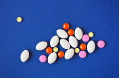 Medicine pills on blue background. Stock Photo